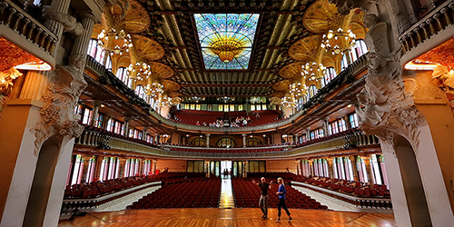 A shot looking from the polished wood stage to the red-velvet audience seating in a soaring, intricate music hall in Barcelona.