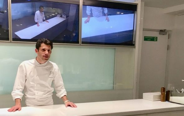 Chef at a demo station with tv screens above him showing different viewpoints of the countertop.