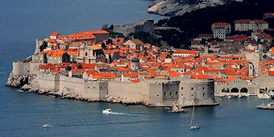Dubrovnik from the water with a wall around the red roofed buildings.