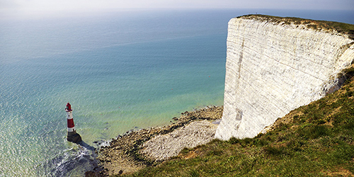 A large, flat white cliff soaring above a red and white lighthouse in Dover.