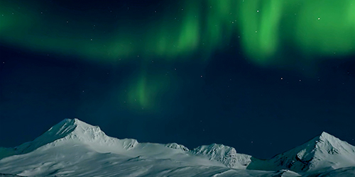 The Northern Lights above snowy mountains