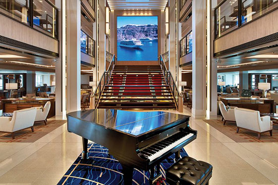 A shiny, black grand piano inside a Viking Ocean ship, in front of the stairs to the second floor.