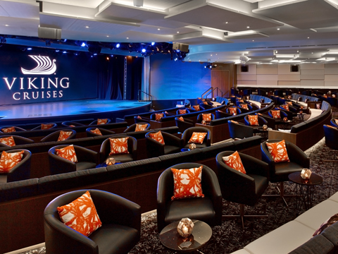 Interior of the Viking Star Theatre, with black chairs, orange throw pillows, and a stage with the Viking Logo in white.