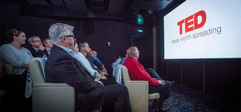 Guests watching a TED Talk on a display