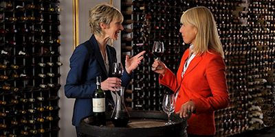 Karine Hagen drinking a glass of red wine with another woman, standing in front of a wall of wine barrels.