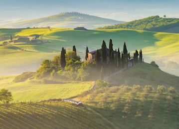 Landscape with misty hills at sunrise in Tuscany