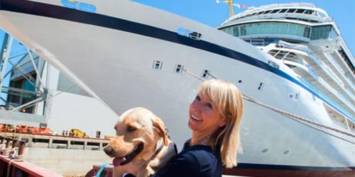 Karine Hagen holding her dog, Finse, in front of a Viking Ocean Ship.