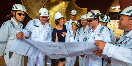 A gathering of happy construction workers looking at the plans for a new Viking Ocean Ship.