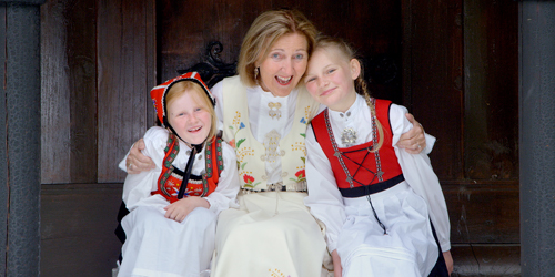 A woman hugging two little girls, dressed in traditional Norweigian garb.