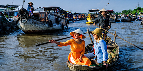 Karine and guest on a traditional Vietnamese river boat