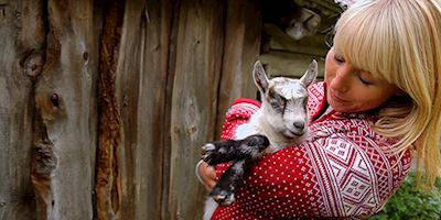 Karine Hagen in a red and white sweater, holding and hugging a baby goat to her chest.