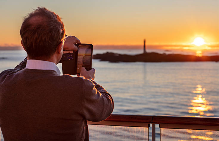 A man taking a photo of a sunset